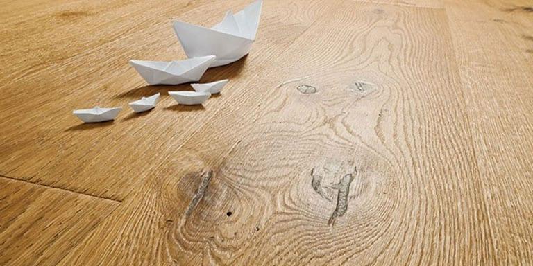 Parquet con nudos profundos y barcos de papel